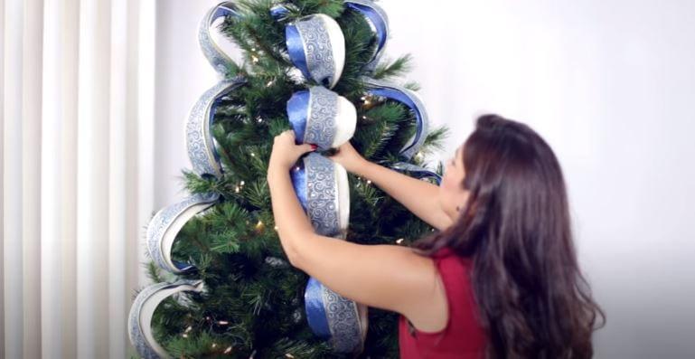 Paso 3 - colocar las cintas para embellecer el árbol navideño como una estilista