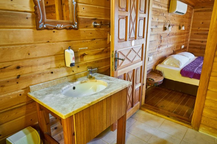 Cuarto de baño de dormitorio con paredes de madera, muebles de madera y lavabo de mármol.