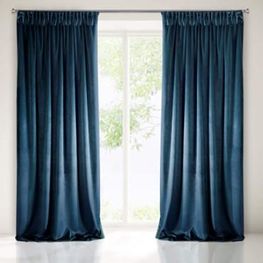 Cortinas de terciopelo azul cubriendo una ventana que da a la terraza.