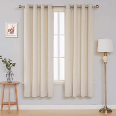 Cortina beige terciopelo para salón dormitorio. Dormitorio interior con cortinas, un cuadro colgado, lámparas y un taburete para plantas decorativo.