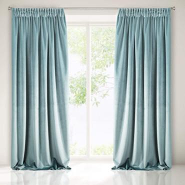 cortinas de terciopelo azul claro colgadas frente una ventana decorando el salón de casa.