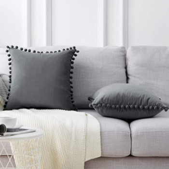 Cojines decorativos de terciopelo gris con borlas, sobre un sofá de color gris plata.