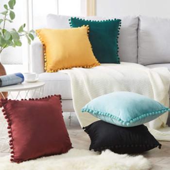 Varios cojines de colores decorativos en un salón con una planta y un sofá precioso.