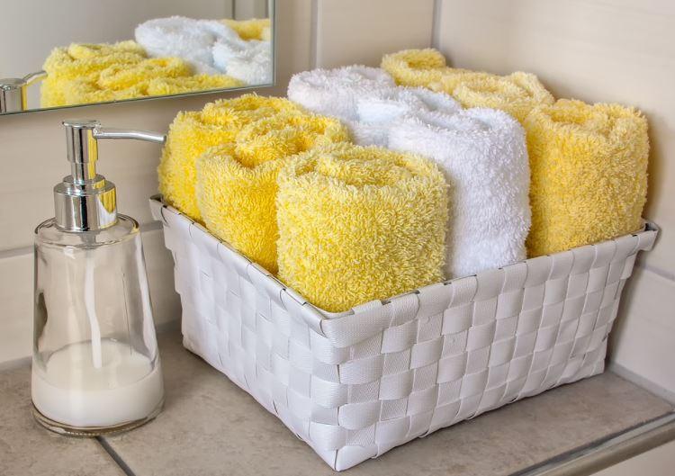 Cesta de mimbre organizando toallas de baño y decorando una encimera del lavabo con tallas de mano para el aseo.