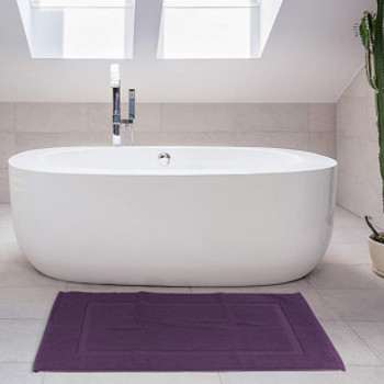 Accesorios de baño: Una alfombrilla de baño de color lavanda bajo una bañera de diseño en un cuarto de baño luminoso.